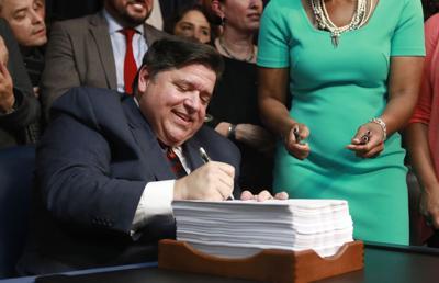 FILE - IL Gov. J.B. Pritzker signing bill (generic)