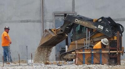 FILE - construction workers build new warehouse on site of former Chrysler plant in Fenton, Missouri