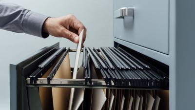 FILE - Office clerk reaches for a file