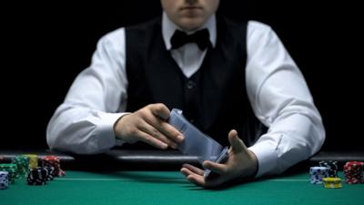 FILE - Card dealer casino worker