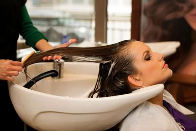 FILE - Hair stylist shampooing, salon, occupational licensing
