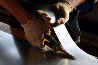worker cuts a stainless sheet with metal shears