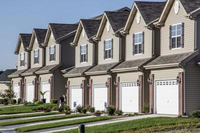FILE - Suburban condominiums, house, property taxes