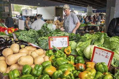 Customers shopping for produce at the farmers market under Bridge in Baltimore, MD