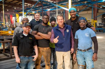 FILE - Gov. Brian Kemp and workers