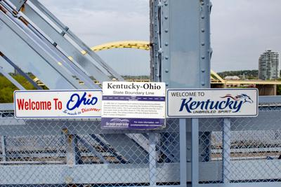 FILE - OH, KY border welcome sign Cincinnati 4-24-2019