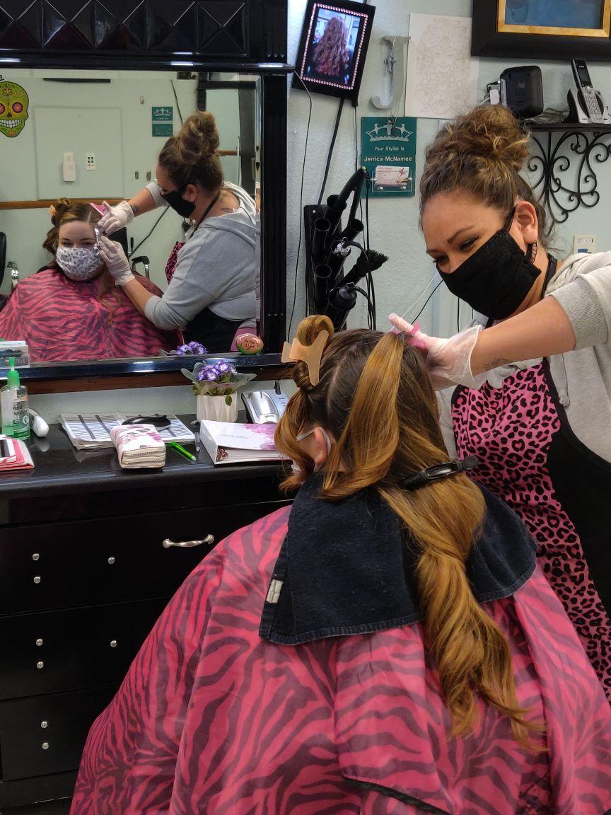 A stylist works on a customer's hair at Enchanted Hair Salon