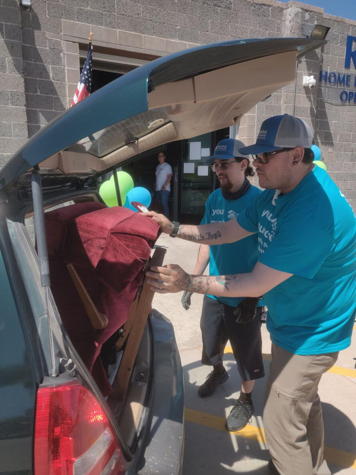 Habitat for Humanity Store Manager Christopher Jounos (L) and Donation Assistant Brandon Wilbourne (R) load a recliner photo