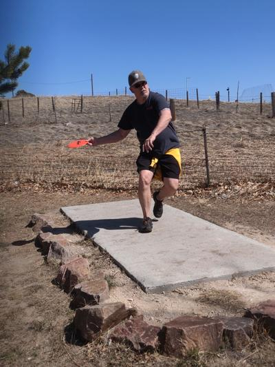 Steve Hanson launches a disc at the Disc Golf Course photo