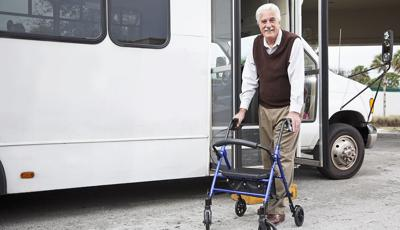 Man using a walker getting into a public transportation van