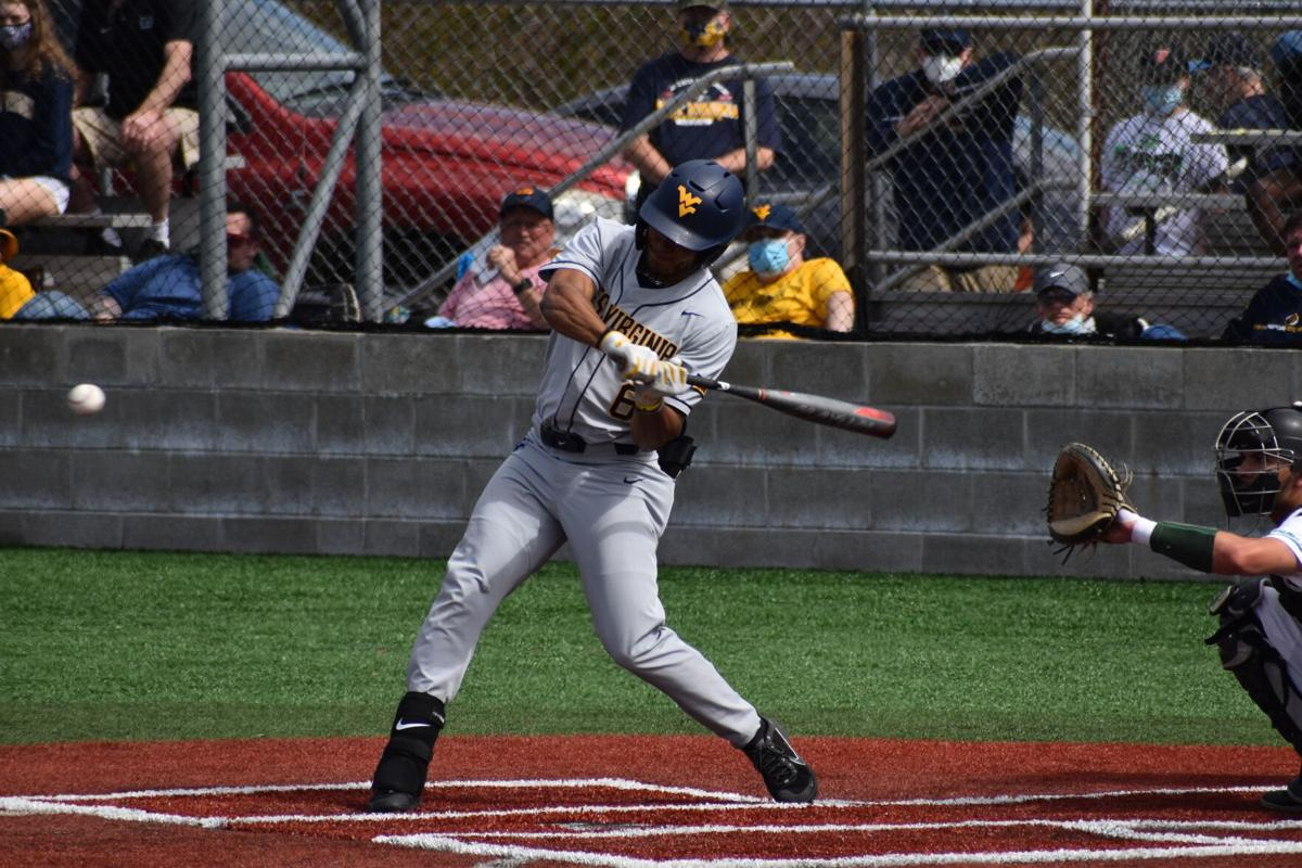 Victor Scott swings at a pitch in West Virginia's loss to Marshall in Huntington, W.Va., on March 23 2021.