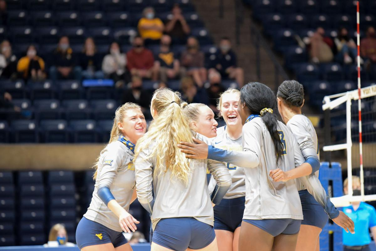 Members of the West Virginia volleyball celebrate scoring a point against Iowa State at the WVU Coliseum on November 6, 2020.
