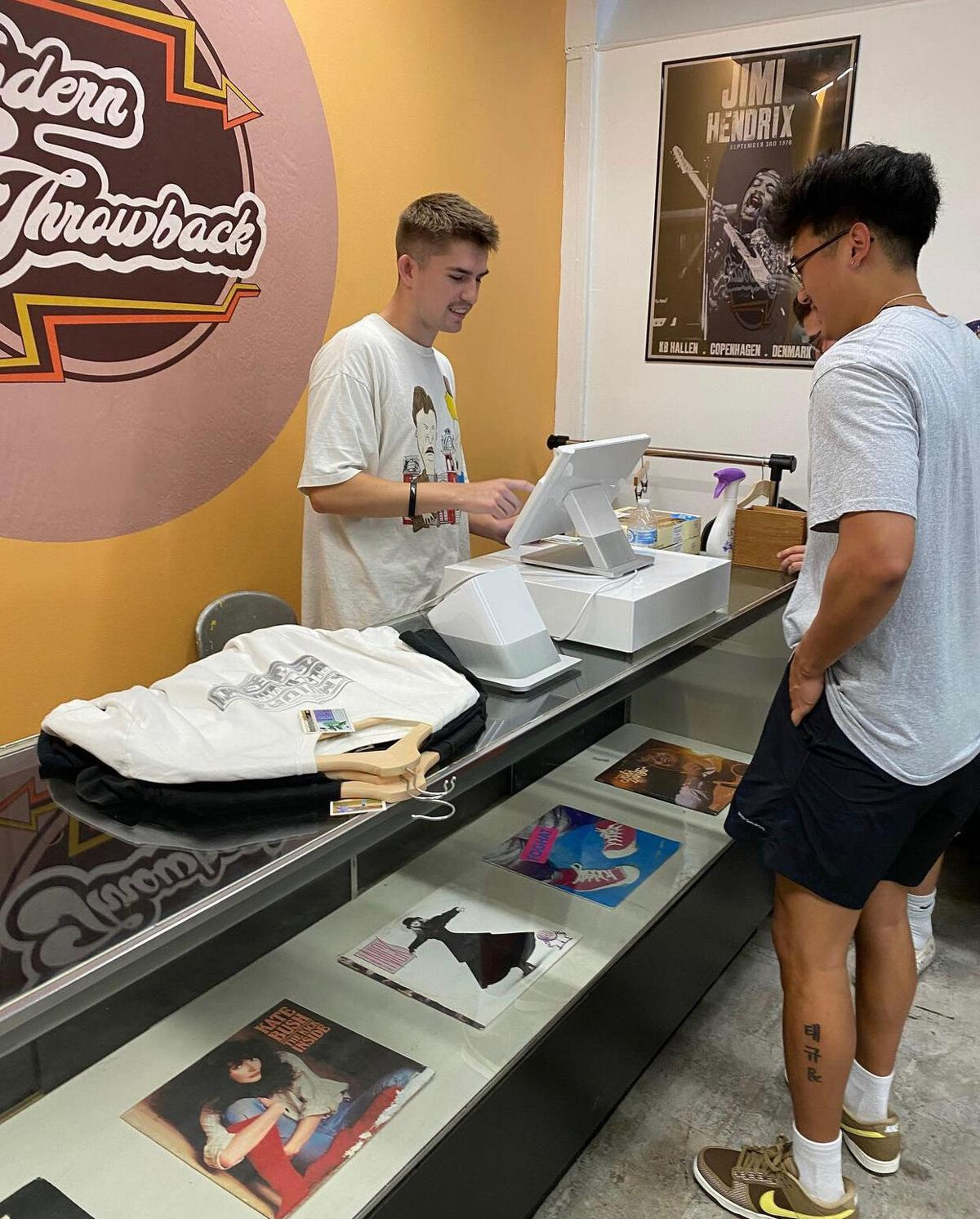 Alum checking out customer in new store