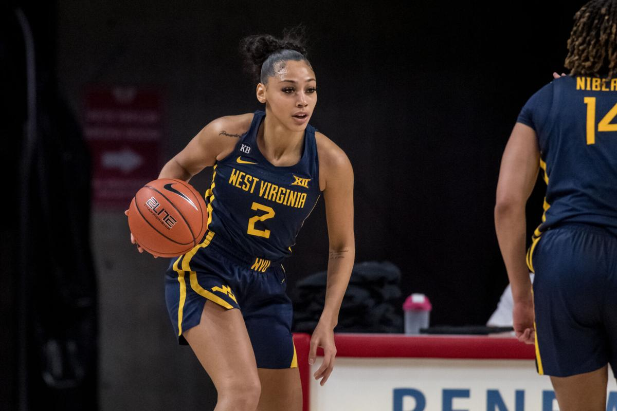 West Virginia guard Kysre Gondrezick (2) takes the ball around the perimeter against the Iowa State Cyclones in Ames, Iowa, on Feb. 24, 2021.