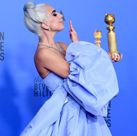 Lady Gaga holding her golden globe and looking like an absolute goddess