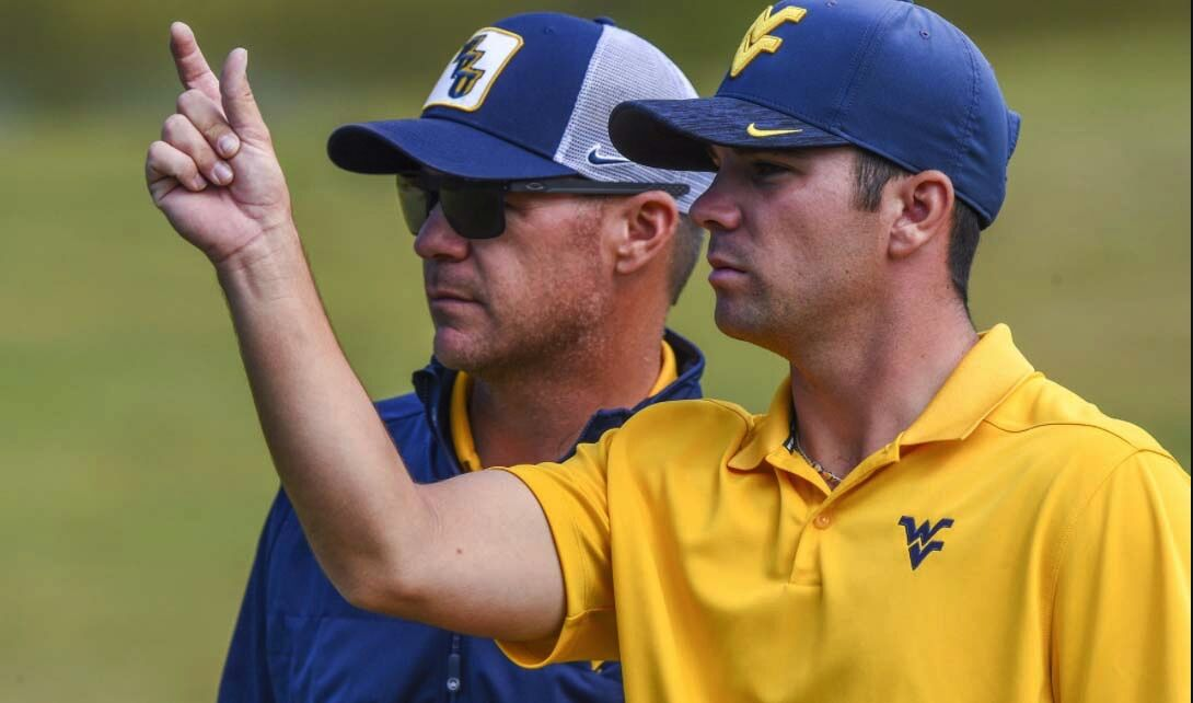 West Virginia golf team member Etienne Papineau (right) talks with head coach Sean Covich during a golf tournament.