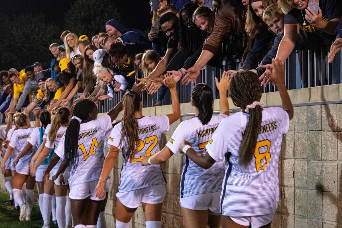 """After a victory over Duquesne, the women's soccer team celebrates with the fans as """"Take Me Home, Country Roads"""" plays."""