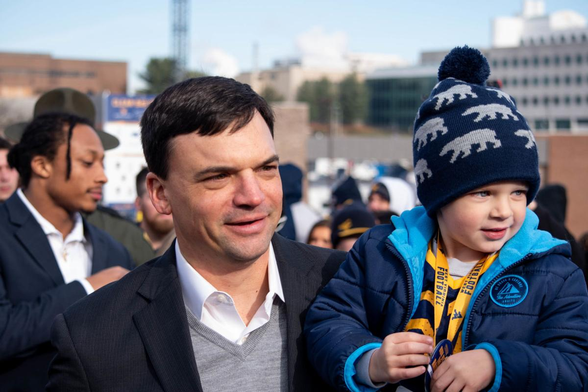 West Virginia head coach Neal Brown enters the stadium with his son during the Mountaineer Mantrip prior to taking on Oklahoma State at Milan Puskar Stadium on Nov. 23, 2019.