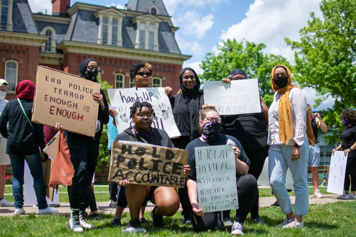 May 30, 2020: Protesters hold up signs during a racial injustice demonstration in front of Woodburn Hall.
