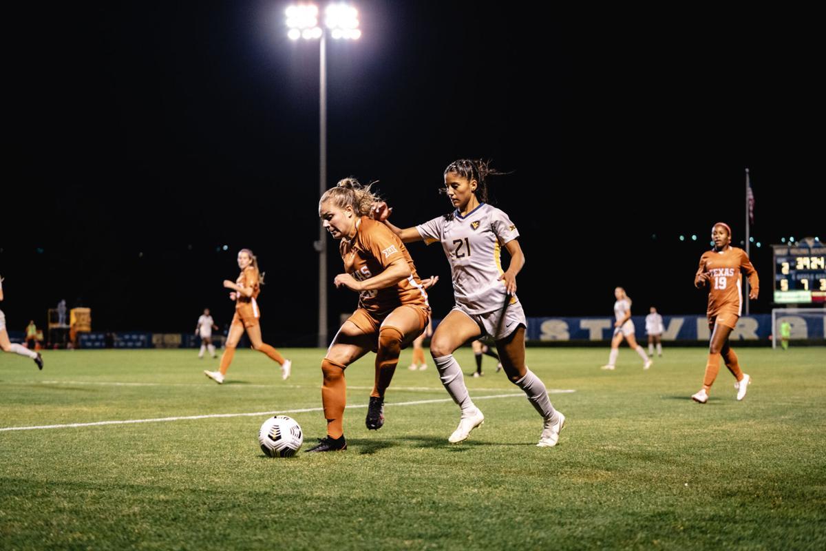WVU midfielder Stefany Ferrer-VanGinkel (21) battles for the ball with Texas defender Emma Regan during the second half on October 2, 2020.
