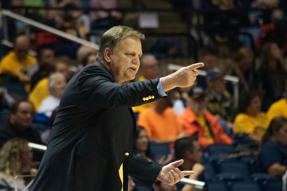 WVU women's basketball head coach Mike Carey yells at his players on the court during their match-up against Coppin State.