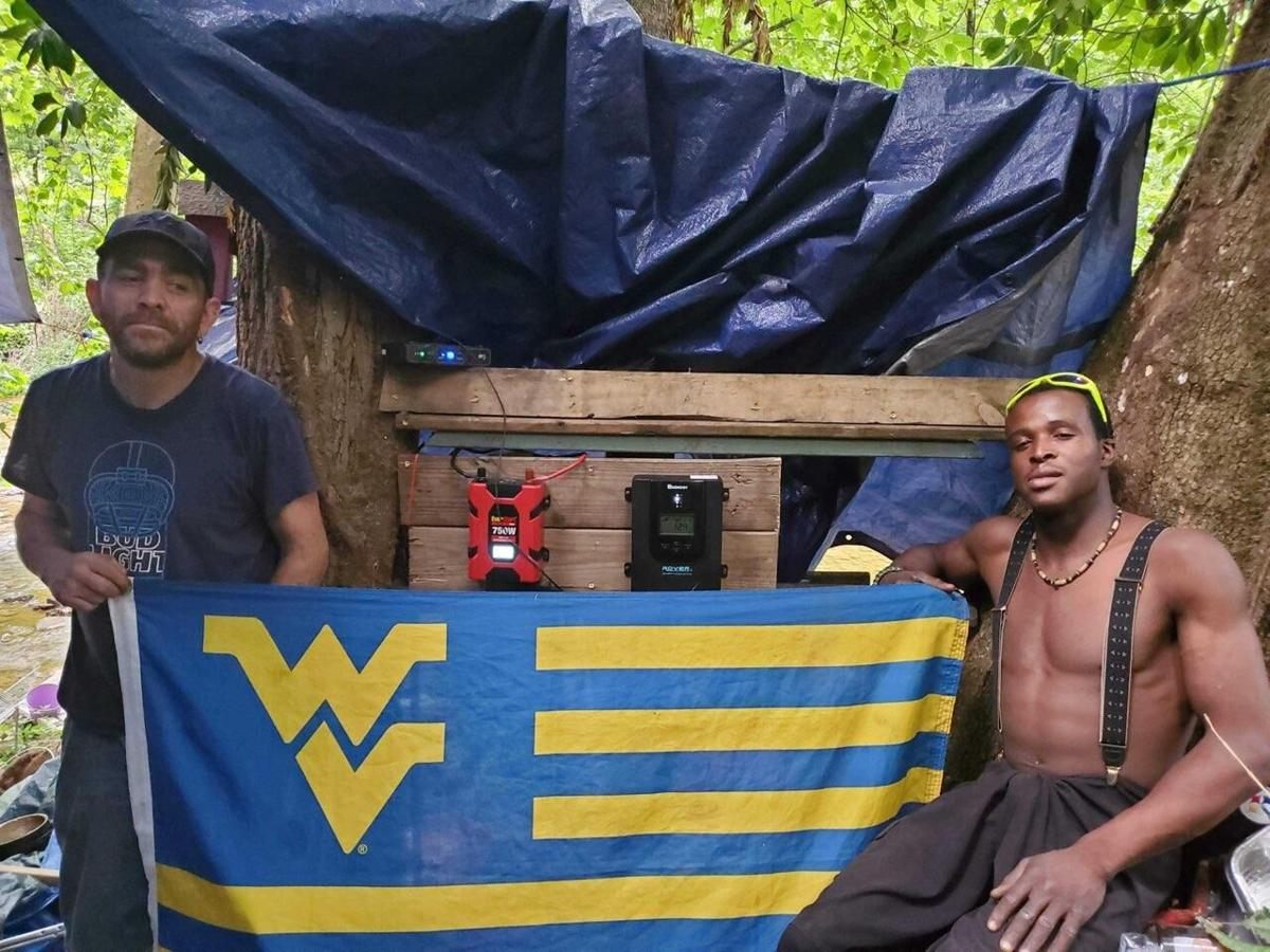 Two residents of Diamond Village, a homeless encampment in Morgantown, hold a WVU flag.