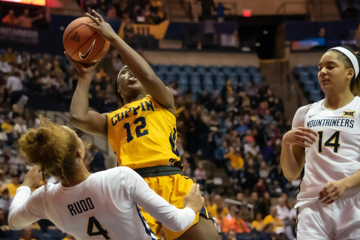 Coppin State forward Oluwadamiola Oloyede races to the basket with WVU senior guard Lucky Rudd and Sophomore Forward Kari Niblack guarding.
