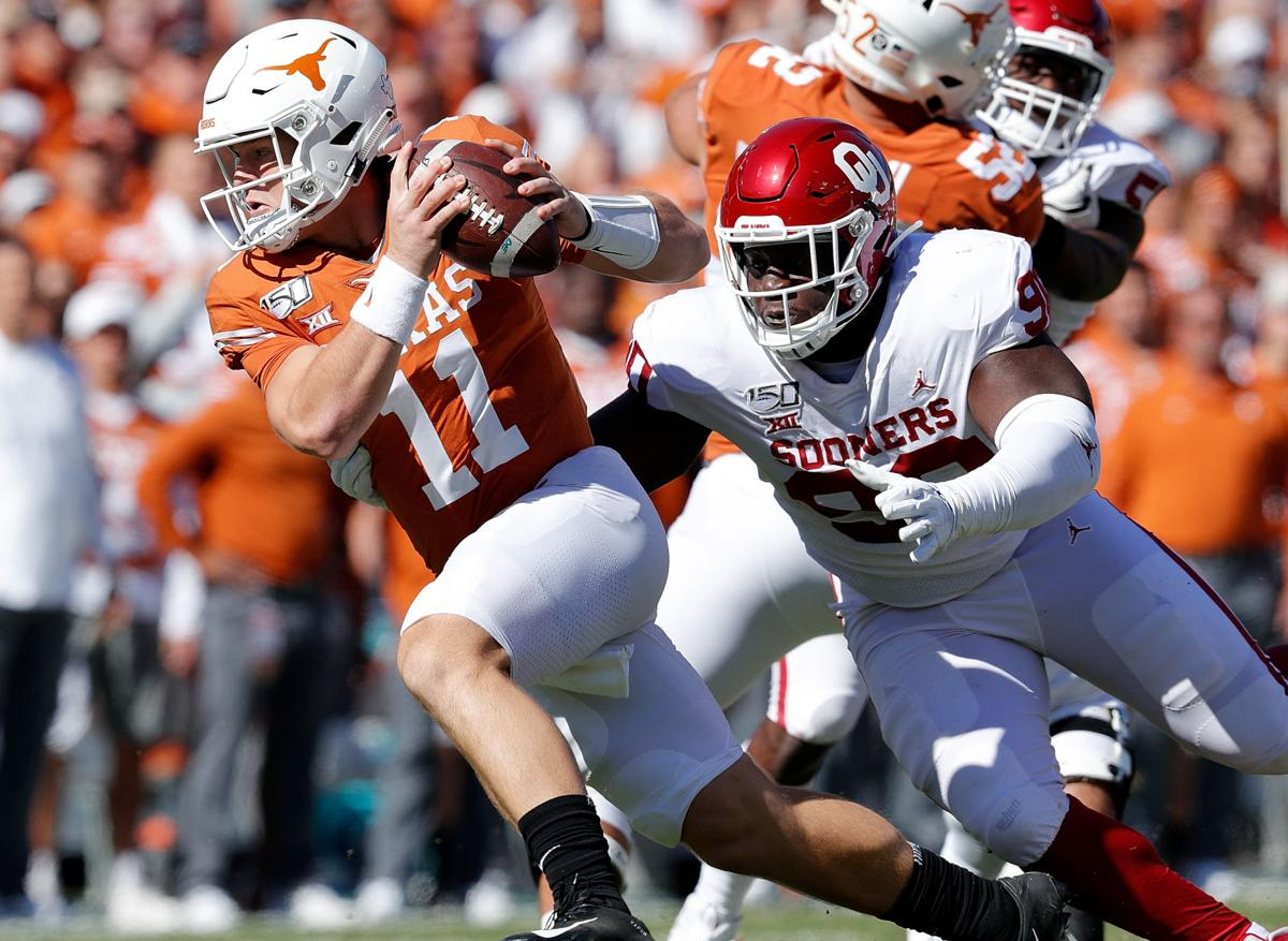 Oklahoma defensive tackle Neville Gallimore (right) chases down Texas quarterback Sam Ehlinger during a 2019 game.