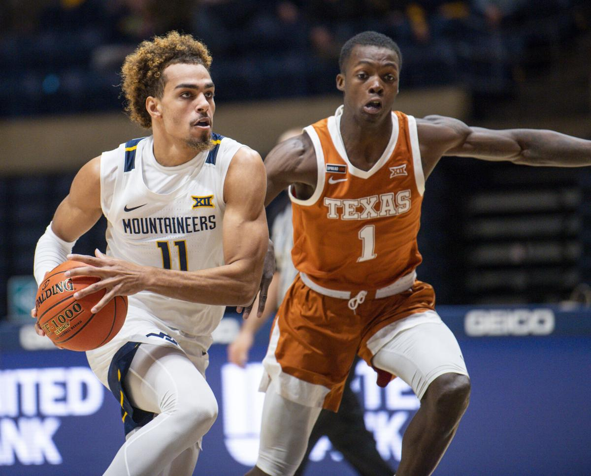 West Virginia's Emmitt Matthews Jr. (11) drives by Texas' Andrew Jones (1) in West Virginia's game against Texas at the WVU Coliseum in Morgantown, W.Va., on Jan. 9, 2021.