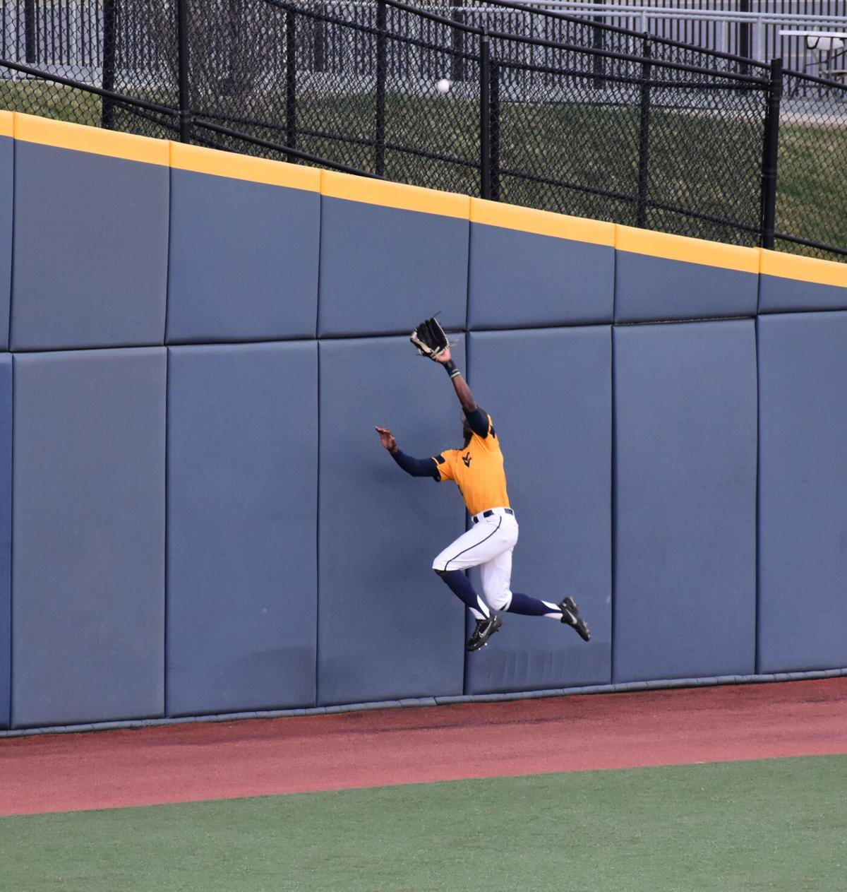 Paul McIntosh leaps for catch at the wall in game two of a doubleheader versus Kansas at the Monongalia County Ballpark in Morgantown, W.Va., on March 27 2021.
