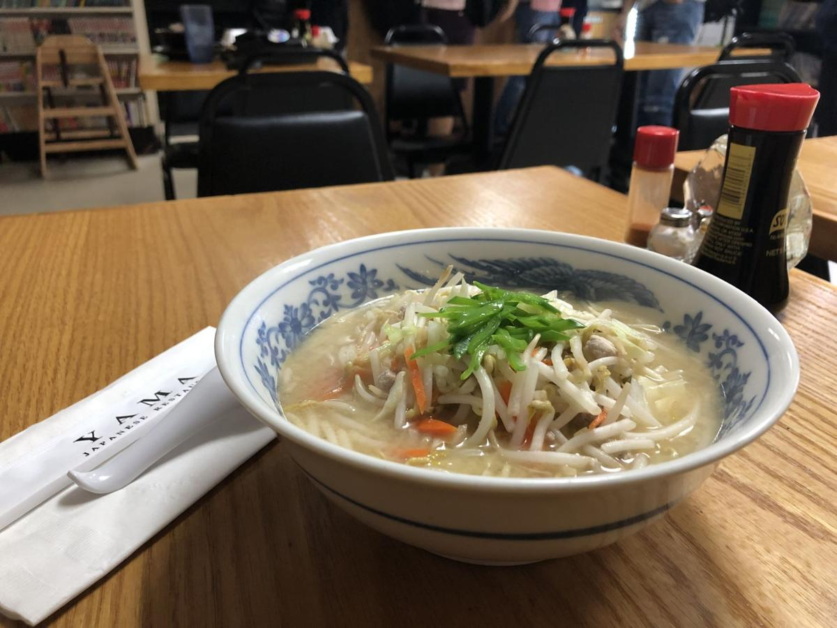 A picture of miso ramen that fills a bowl in a restaurant.