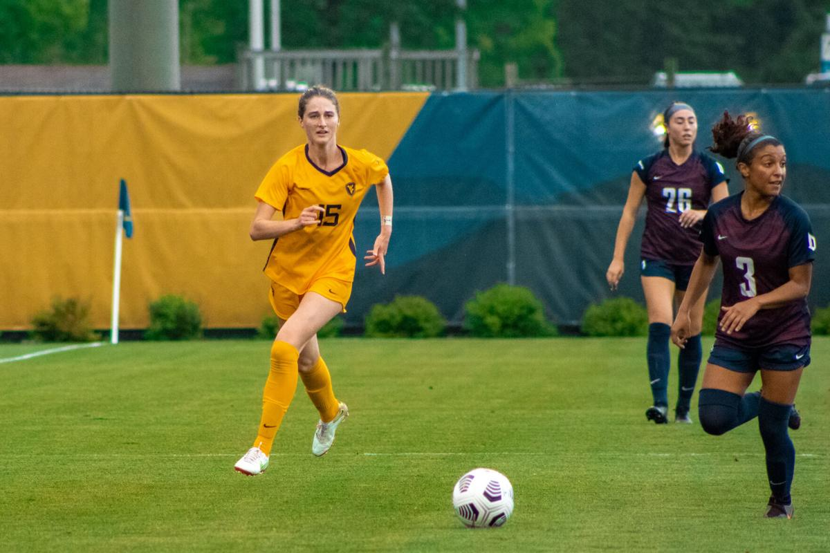 West Virginia's Lilly McCarthy (15) drives the ball down the sideline against Duquesne at Dick Dlesk Soccer Stadium in Morgantown, W.Va., on Aug. 29, 2021.