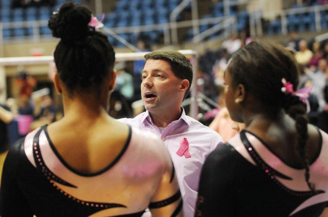 WVU head gymnastics coach Jason Butts talks to his team during a competition.