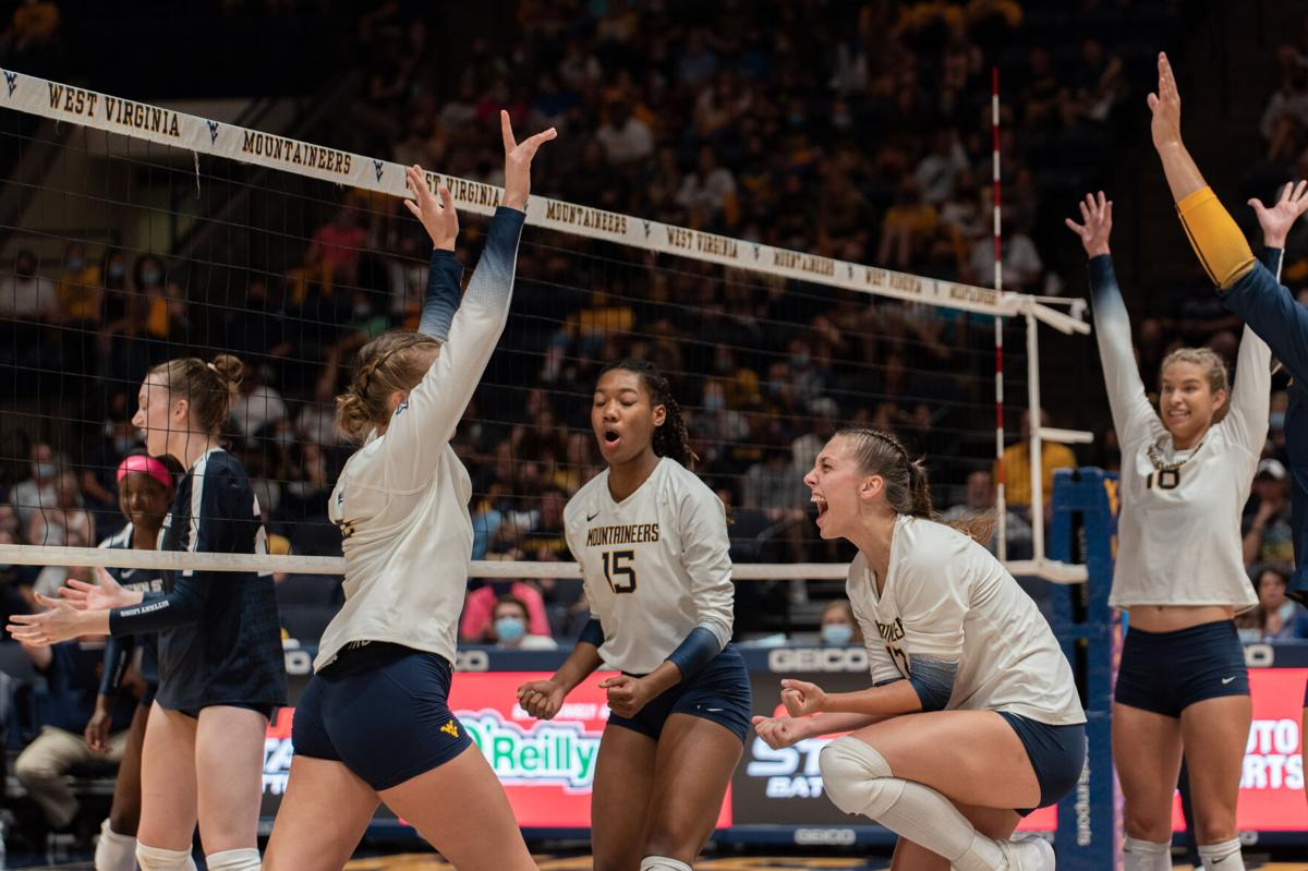 The WVU volleyball team celebrates a point against Penn State on Sept. 17, 2021.
