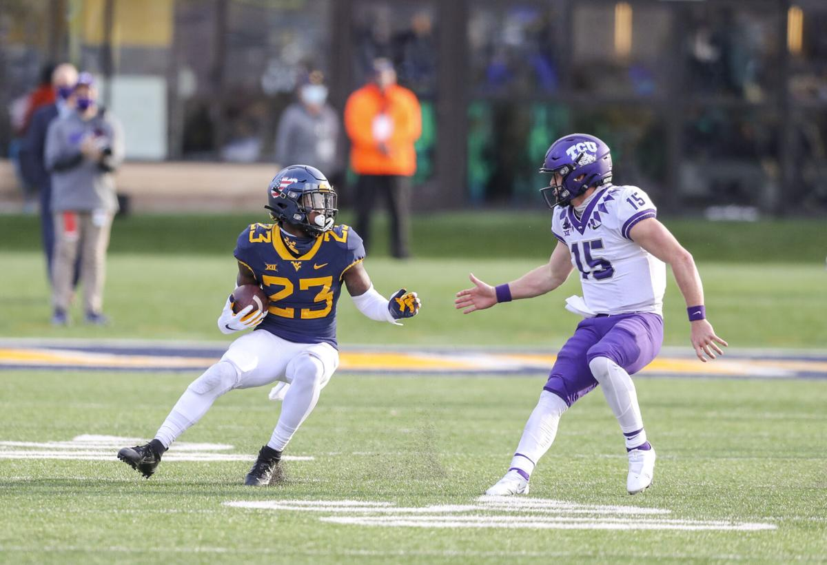 Nov 14, 2020; Morgantown, West Virginia, USA; West Virginia Mountaineers safety Tykee Smith (23) intercepts a pass from TCU Horned Frogs quarterback Max Duggan (15) and runs for extra yards during the fourth quarter at Mountaineer Field at Milan Puskar Stadium.
