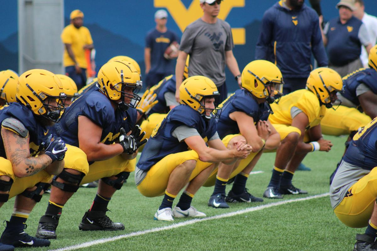 Members of the WVU football team stretch before practice.