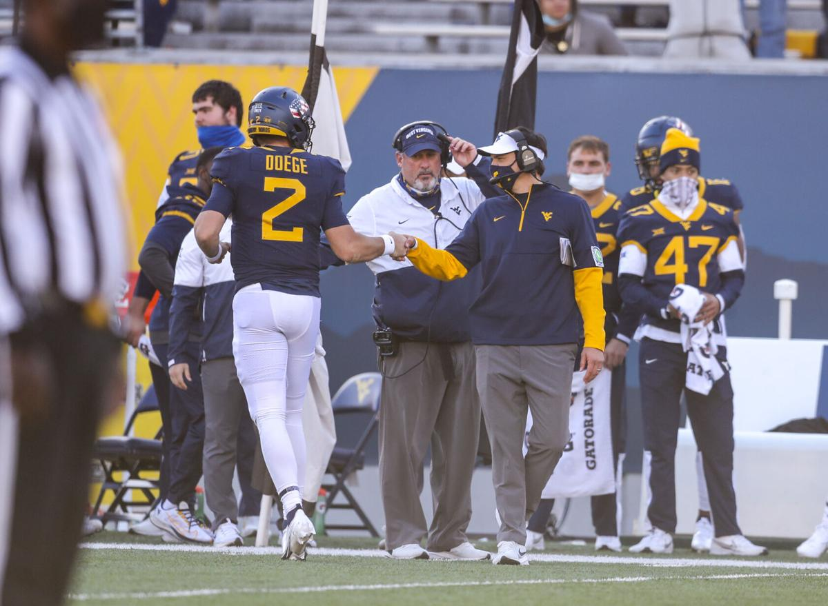 Nov 14, 2020; Morgantown, West Virginia, USA; West Virginia Mountaineers quarterback Jarret Doege (2) celebrates with West Virginia Mountaineers head coach Neal Brown after throwing a touchdown during the fourth quarter against the TCU Horned Frogs at Mountaineer Field at Milan Puskar Stadium.