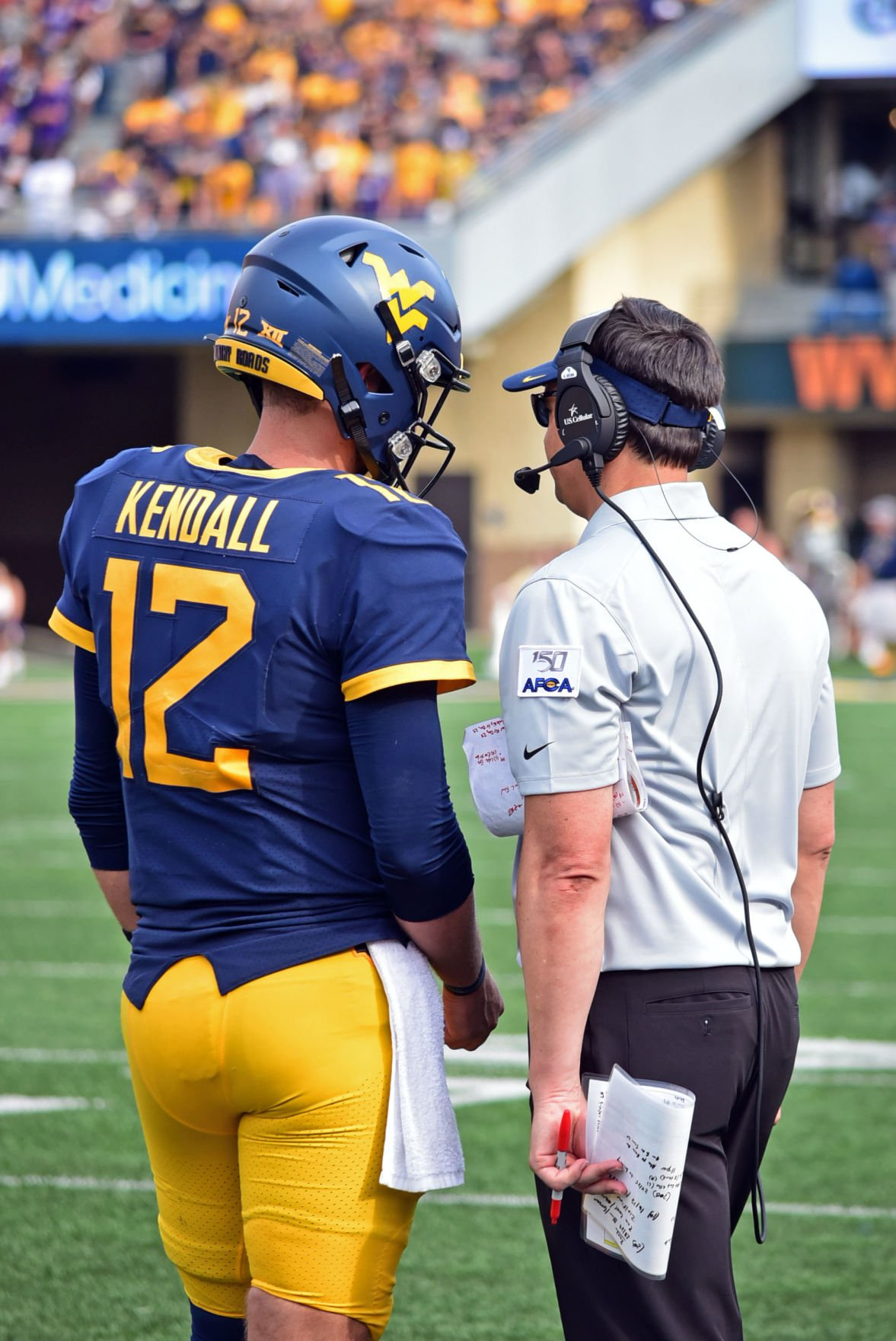 Quarterback Austin Kendall meets on the sideline with head coach Neal Brown to discuss the next play against JMU.