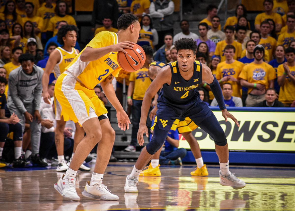 West Virginia guard Miles McBride (blue) stares down Pittsburgh's Trey McGowens during the first half at Petersen Events Center on Nov. 15, 2019.