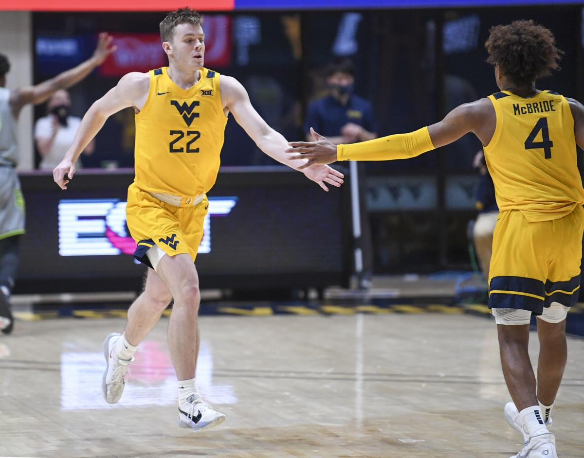 West Virginia guards Sean McNeil (22) and Miles McBride (4) high-five mid-game against Baylor on March 2, 2021.