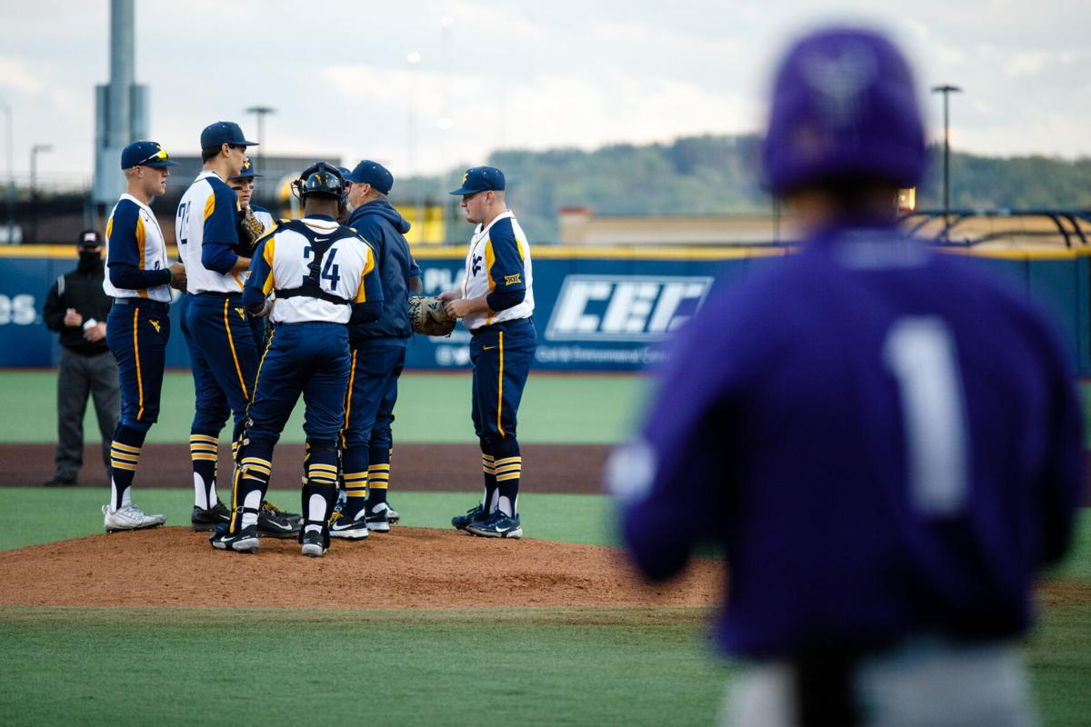 WVU players confer at the mound during West Virginia's game against the TCU Horned Frogs on April 30, 2021.