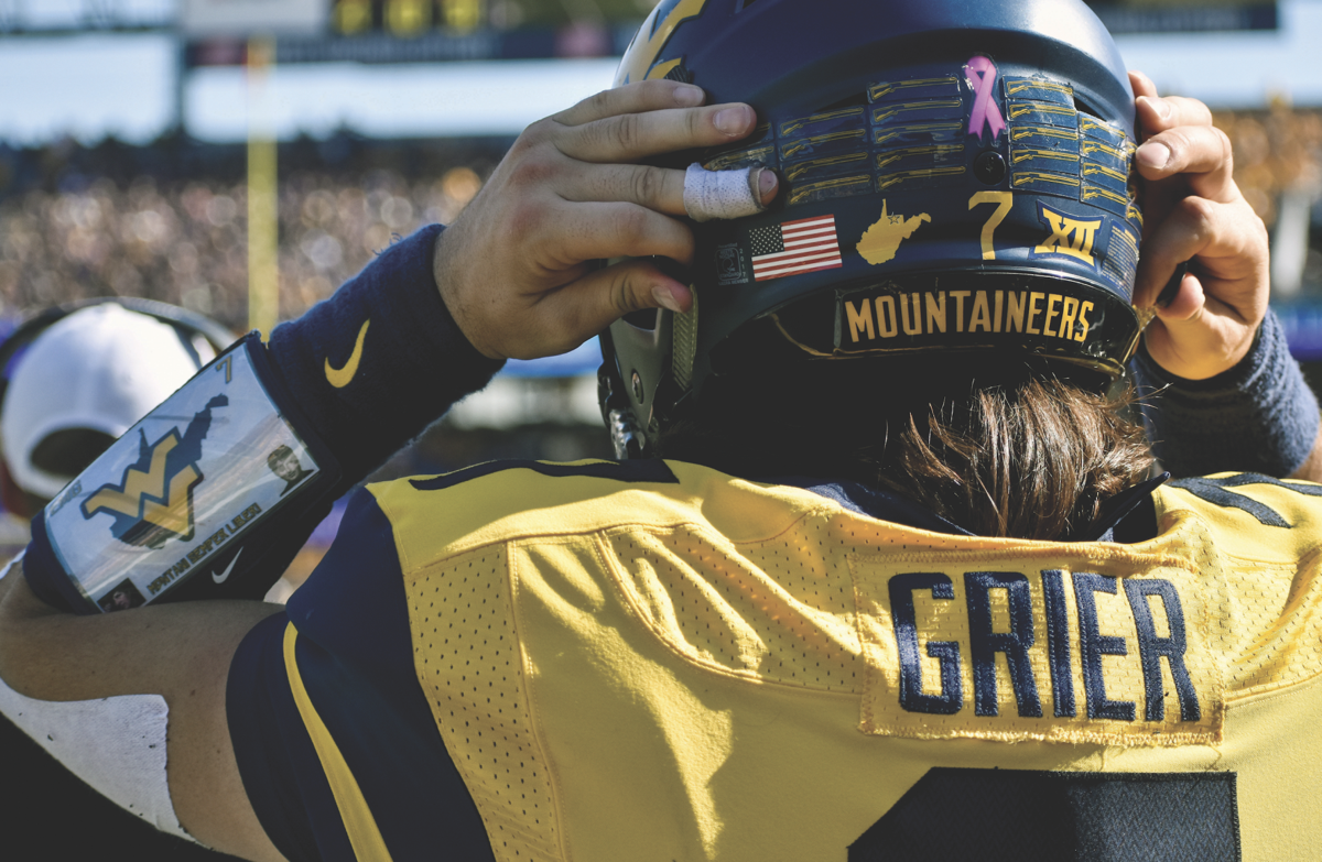 Will Grier adjusting his helmet strap before his play.