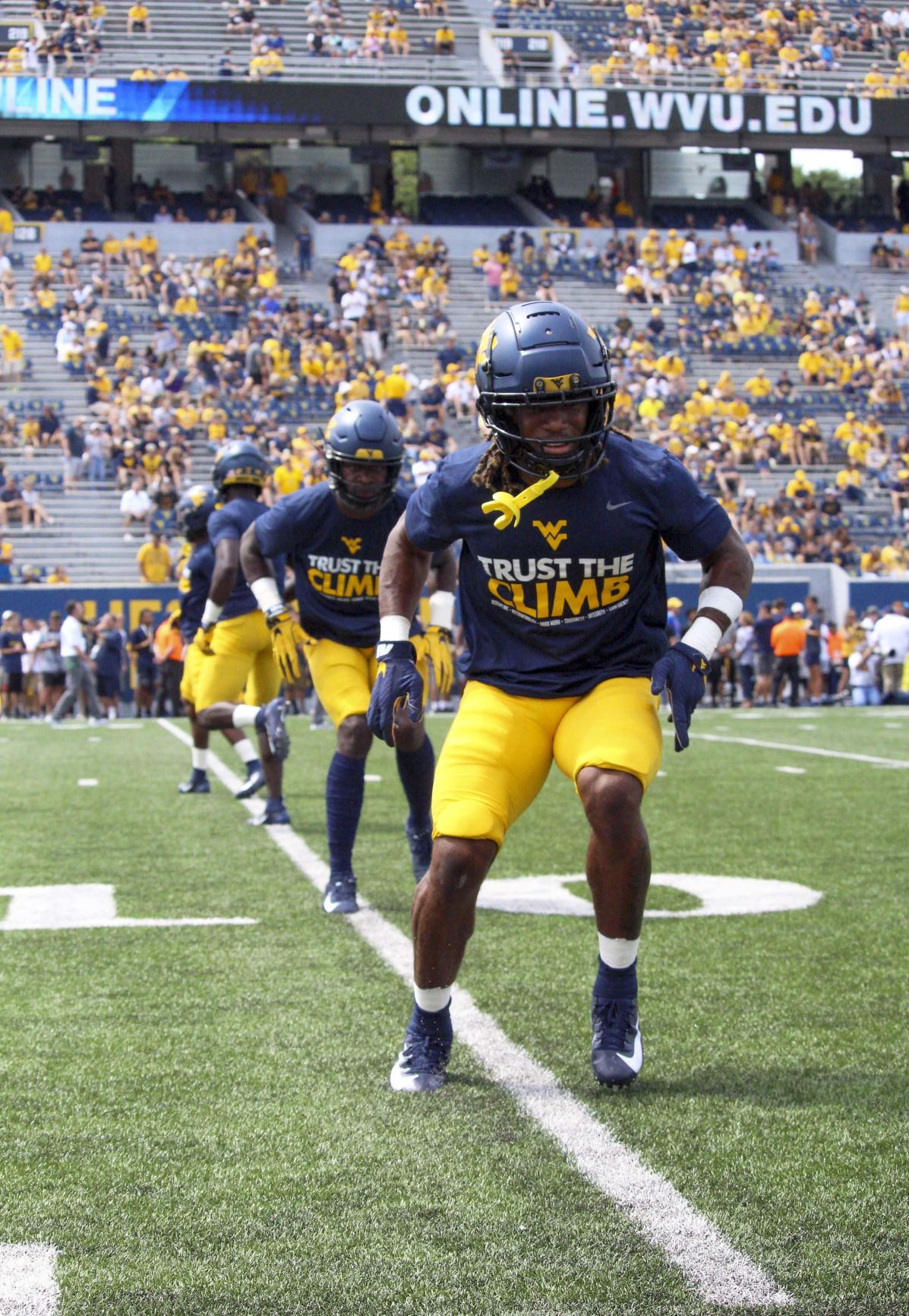 Members of the West Virginia football team go through pregame warmups.