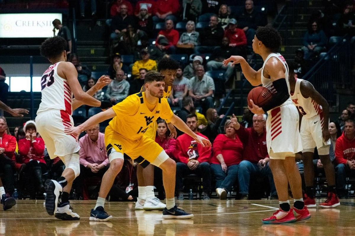 West Virginia guard Chase Harler (14) defends Youngstown State guard Darius Quisenberry at the Covelli Centre on Dec. 21, 2019.