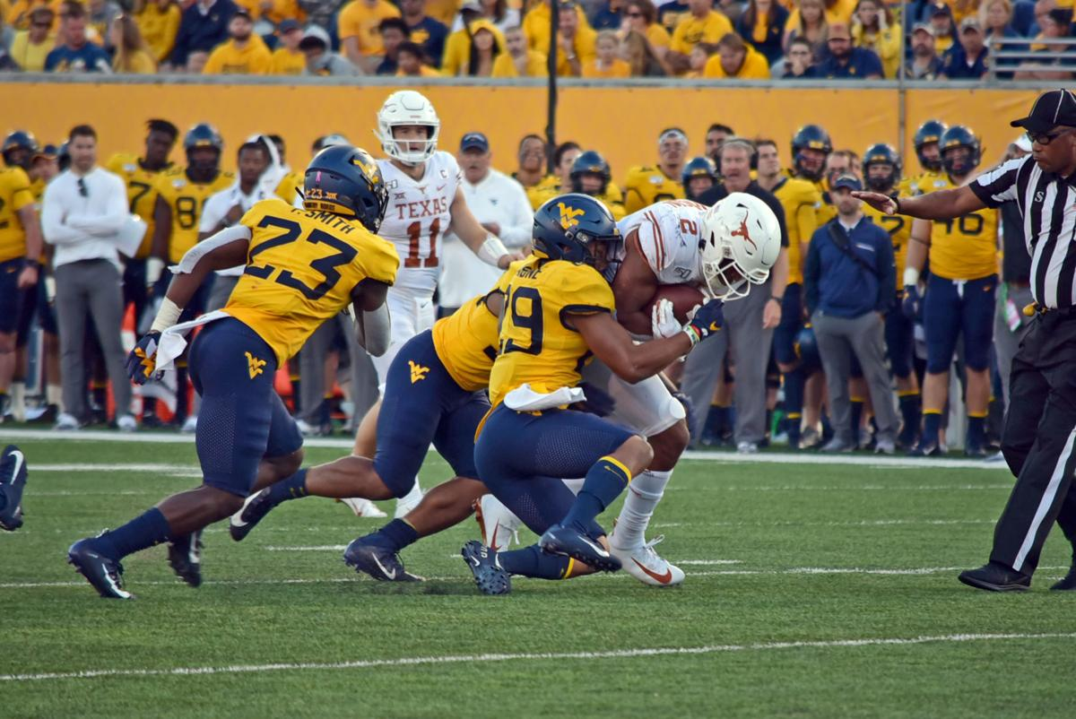 Redshirt Junior Sean Mahone tackles a Texas Longhorn player on the play.