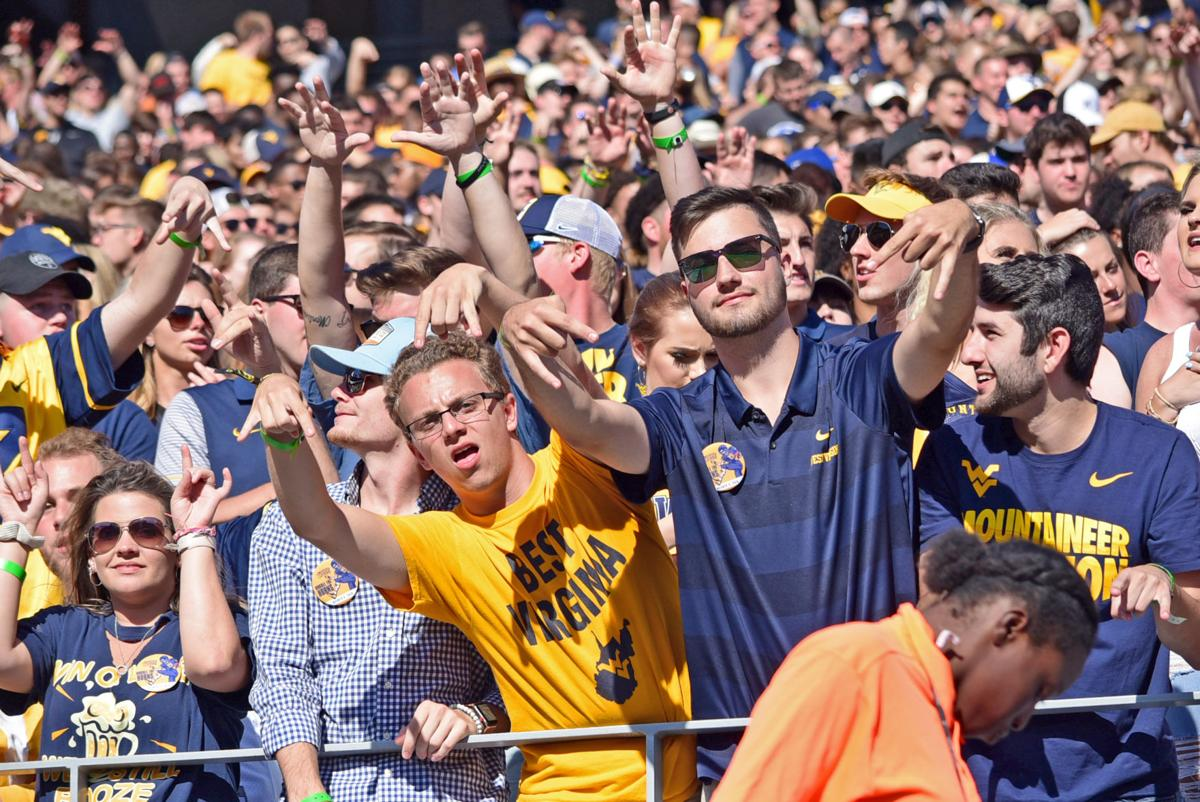 West Virginia University fans sport the 'horns down' hand signal during the match-up against Texas.