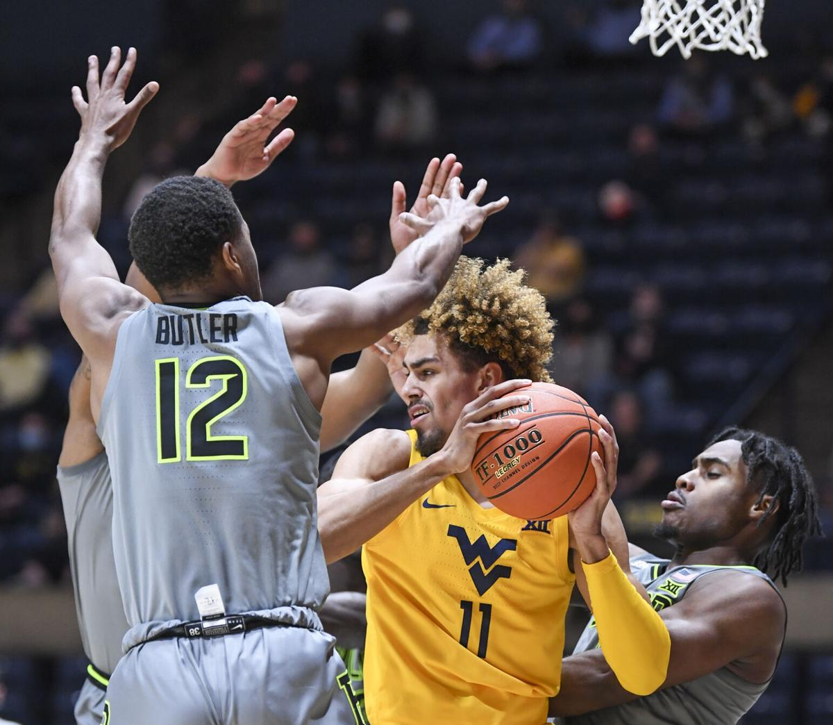 West Virginia forward Emmitt Matthews Jr. (11) is guarded by Baylor's Jared Butler (12) in WVU's loss against Baylor on March 2, 2021.