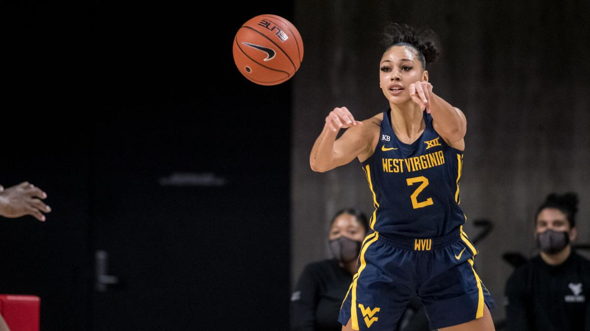 West Virginia guard Kysre Gondrezick passes the ball to her teammate against the Iowa State Cyclones on Feb. 24, 2021.