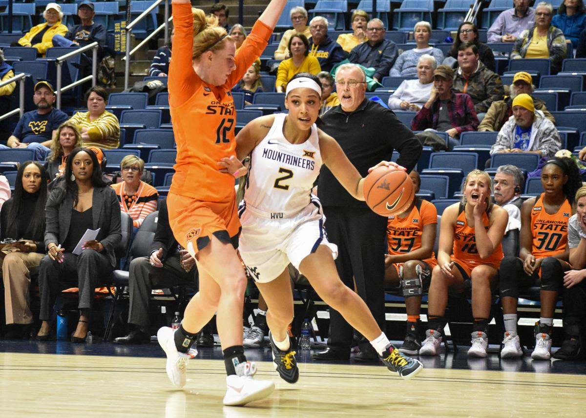 Jan. 22nd 2020 - Redshirt Junior Guard Kyrse Gondrezick looks to get past Oklahoma States Vivian Gray at the Coliseum