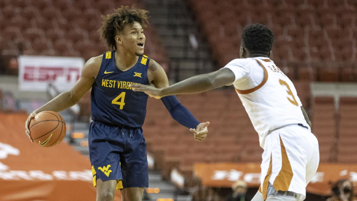 West Virginia guard Miles McBride (4) directs the Mountaineers against the Texas Longhorns in Austin, Texas, on Feb. 20, 2021.